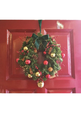 Photograph of an artificial Christmas wreath decorated in Nordic theme decorations with a gold star: orange, red, and gold baubles with artificial red berries, cinnamon sticks, pinecones and oranges. The wreath has a green ribbon, and is hung on a red panelled door. Office Christmas Decor; Christmas decorations, Christmas florist, Office decorations, Xmas decorations, Christmas tree, Artificial Christmas tree, Real Christmas tree. Office Christmas; Christmas decorators Wreath making; bespoke Christmas Decor