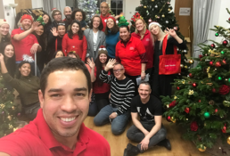 Photograph of Sparkle Team members wearing red shirts. Office Christmas Decor; Christmas decorations, Christmas florist, Office decorations, Xmas decorations, Christmas tree, Artificial Christmas tree, Real Christmas tree. Office Christmas; Christmas decorators Wreath making; bespoke Christmas Decor.