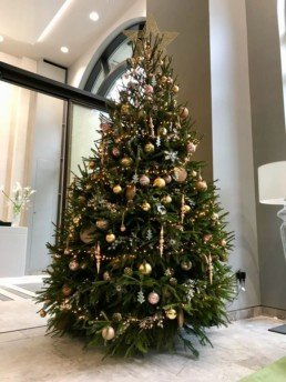 Photograph of an 8ft real Christmas Tree decorated in Bespoke Emerald-theme decorations: with a gold star, ceramic Christmas trees, rose gold accessories and blush pink baubles, at an office building in Central London. Office Christmas Decor; Christmas decorations, Christmas florist, Office decorations, Xmas decorations, Christmas tree, Artificial Christmas tree, Real Christmas tree. Office Christmas; Christmas decorators Wreath making; bespoke Christmas Decor.