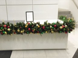 Photograph of a close-up of an artificial Christmas garland decorated in Traditional theme decorations with a gold star: green, red and gold baubles with artificial red berries, cinnamon sticks, pinecones and gold eucalyptus. The garland is wrapped around the corner of a desk. Office Christmas Decor; Christmas decorations, Christmas florist, Office decorations, Xmas decorations, Christmas tree, Artificial Christmas tree, Real Christmas tree. Office Christmas; Christmas decorators Wreath making; bespoke Christmas Decor.