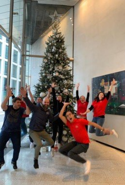 Photograph of 8 Sparkle Team members jumping in front of an 18ft real Christmas Tree decorated in Frozen Woodland decorations with a silver star: silver and white baubles of assorted sizes, with silver twigs, snowflakes, white iridescent hanging strings of pearls, cinnamon sticks and pinecones. Beneath the tree are silver presents wrapped in silver and red ribbon, and bundles of silver twigs. Office Christmas Decor; Christmas decorations, Christmas florist, Office decorations, Xmas decorations, Christmas tree, Artificial Christmas tree, Real Christmas tree. Office Christmas; Christmas decorators Wreath making; bespoke Christmas Decor.