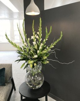 Photograph of lily bud heads inside a clear, round stacked vase, with white gladioli and white twigs, on a black table. Beside the table is a grey sofa with emerald velvet textured cushion. Corporate florist, event flowers, office flowers, sustainable florist, Central London florist, Local florist, Soho Florist, Contemporary Floral Display. Weekly Office Flowers; Weekly Flowers; Weekly Contract Flowers; Reception Desk Flowers; Office Reception Flowers