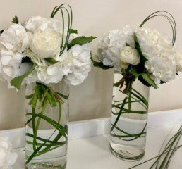 Photograph of white hydrangeas and white roses in clear, cylinder vases on a table. Corporate florist, event flowers, office flowers, sustainable florist, Central London florist, Local florist, Soho Florist, Contemporary Floral Display. Weekly Office Flowers; Weekly Flowers; Weekly Contract Flowers; Reception Desk Flowers; Office Reception Flowers