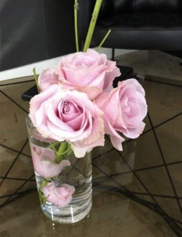 Photograph of 3 pink roses calla lilies in a short, clear cylinder vase, on a glass table. There are pink roses immersed in the water inside the vase. Corporate florist, event flowers, office flowers, sustainable florist, Central London florist, Local florist, Soho Florist, Contemporary Floral Display. Weekly Office Flowers; Weekly Flowers; Weekly Contract Flowers; Reception Desk Flowers; Office Reception Flowers