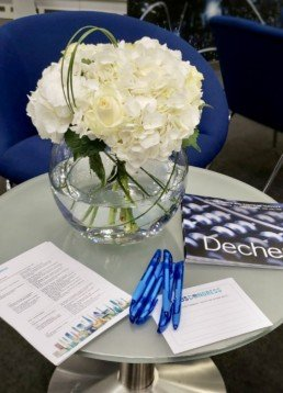 Photograph of event flowers: white hydrangeas in a clear, round vase on a table with pens and company brochure. Corporate florist, event flowers, office flowers, sustainable florist, Central London florist, Local florist, Soho Florist, Contemporary Floral Display. Weekly Office Flowers; Weekly Flowers; Weekly Contract Flowers; Reception Desk Flowers; Office Reception Flowers