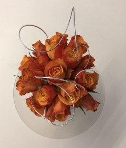 Photograph of orange roses seen from above, with silver wire arranged around them, inside a clear, round vase. Corporate florist, event flowers, office flowers, sustainable florist, Central London florist, Local florist, Soho Florist, Contemporary Floral Display. Weekly Office Flowers; Weekly Flowers; Weekly Contract Flowers; Reception Desk Flowers; Office Reception Flowers