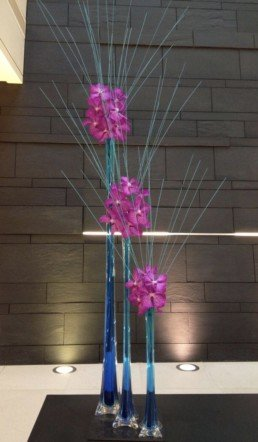 Photograph of pink orchids inside 3 tall, cone-shaped vases, with tall grass arranged in a fan and blue dye in the water. Corporate florist, event flowers, office flowers, sustainable florist, Central London florist, Local florist, Soho Florist, Contemporary Floral Display. Weekly Office Flowers; Weekly Flowers; Weekly Contract Flowers; Reception Desk Flowers; Office Reception Flowers