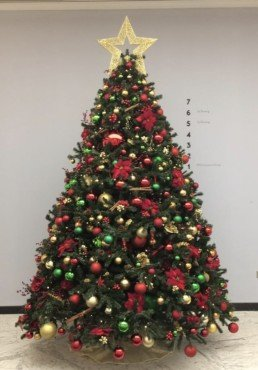 Photograph of a close-up of an artificial 10ft Christmas tree decorated in Traditional theme decorations with a gold star: green, red and gold baubles with artificial red berries, cinnamon sticks, pinecones, red roses and gold eucalyptus. Beneath the tree is a gold skirt. Office Christmas Decor; Christmas decorations, Christmas florist, Office decorations, Xmas decorations, Christmas tree, Artificial Christmas tree, Real Christmas tree. Office Christmas; Christmas decorators Wreath making; bespoke Christmas Decor.