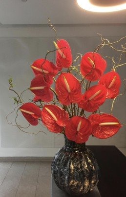 Photograph of red anthuriums and brown willow branches inside a textured metal vase. Corporate florist, event flowers, office flowers, sustainable florist, Central London florist, Local florist, Soho Florist, Contemporary Floral Display. Weekly Office Flowers; Weekly Flowers; Weekly Contract Flowers; Reception Desk Flowers; Office Reception Flowers