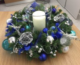 Photograph of an artificial Christmas wreath on a table, decorated in Northern Lights theme decorations with a candle in the centre: silver, blue and teal baubles, glitter accessories including silver roses, jewelled dragonflies, silver eucalyptus, white pearls and silver peacock feathers. Office Christmas Decor; Christmas decorations, Christmas florist, Office decorations, Xmas decorations, Christmas tree, Artificial Christmas tree, Real Christmas tree. Office Christmas; Christmas decorators Wreath making; bespoke Christmas Decor