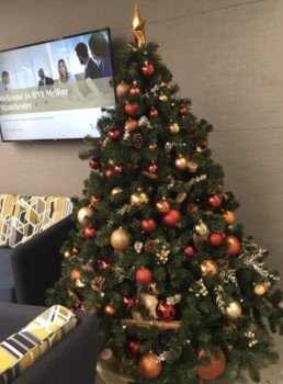 Photograph of an 8ft artificial Christmas tree decorated in Nordic theme decorations with an orange star: orange, red, grey and gold baubles with artificial red berries, cinnamon sticks, pinecones and oranges. Beneath the tree is a gold skirt. Behind the tree is a television screen that says Welcome to BNY Mellon, and a grey sofa. Office Christmas Decor; Christmas decorations, Christmas florist, Office decorations, Xmas decorations, Christmas tree, Artificial Christmas tree, Real Christmas tree. Office Christmas; Christmas decorators Wreath making; bespoke Christmas Decor.