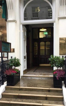 Photograph of vibrant winter plant maintenance for Savile Row, London, with pink Heather, hot pink Cyclamen and structured bay trees, in troughs either side of an open doorway. Mayfair; Luxury London; Soho Florist; Contract planting; plant Maintenance; landscaping; Corporate plants