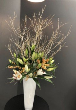 Photograph of white lily bud heads beginning to open, with orange berries and gold twigs, in a tall, white cylinder vase. Corporate florist, event flowers, office flowers, sustainable florist, Central London florist, Local florist, Soho Florist, Contemporary Floral Display. Weekly Office Flowers; Weekly Flowers; Weekly Contract Flowers; Reception Desk Flowers; Office Reception Flowers