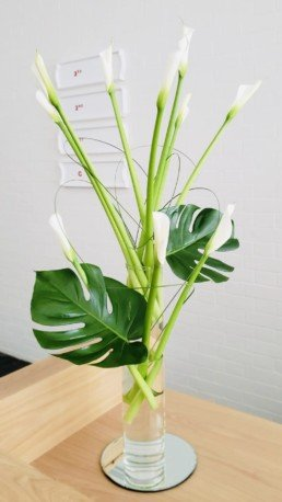 Photograph of white calla lilies, grass and 2 cheeseplant (monstera delicosa) leaves, inside a tall, clear cylinder vase, placed on top of a circular mirror. Corporate florist, event flowers, office flowers, sustainable florist, Central London florist, Local florist, Soho Florist, Contemporary Floral Display. Weekly Office Flowers; Weekly Flowers; Weekly Contract Flowers; Reception Desk Flowers; Office Reception Flowers