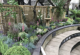 Photograph of an English Courtyard Garden design created for St Annes Church in Soho for the shady area of the vestry garden, including lavender, geranium, hollyhocks, hostas and rosemary. Sustainable gardener; Landscaping; Contract planting; plant maintenance; landscape design, Soho garden; Soho Florist; landscaping; tranquil space