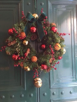Photograph of an artificial Christmas wreath decorated in Nordic theme decorations with a gold star: orange, red, grey and gold baubles with artificial red berries, cinnamon sticks, pinecones and oranges. The wreath has a green ribbon, and is hung on a green panelled door. Office Christmas Decor; Christmas decorations, Christmas florist, Office decorations, Xmas decorations, Christmas tree, Artificial Christmas tree, Real Christmas tree. Office Christmas; Christmas decorators Wreath making; bespoke Christmas Decor.