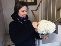 Storm Flowers florist arranging white hydrangeas in a clear round vase. Corporate florist, event flowers, office flowers, sustainable florist, Central London florist, Local florist, Soho Florist, Contemporary Floral Display. Weekly Office Flowers; Weekly Flowers; Weekly Contract Flowers; Reception Desk Flowers; Office Reception Flowers