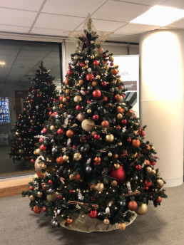 Photograph of an 8ft artificial Christmas tree decorated in Nordic theme decorations with a gold star: orange, red, grey and gold baubles with artificial red berries, cinnamon sticks, pinecones and oranges. Beneath the tree is a gold skirt. Office Christmas Decor; Christmas decorations, Christmas florist, Office decorations, Xmas decorations, Christmas tree, Artificial Christmas tree, Real Christmas tree. Office Christmas; Christmas decorators Wreath making; bespoke Christmas Decor