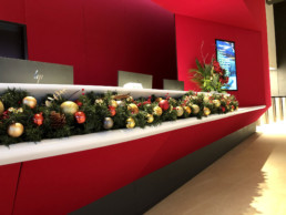 Photograph of a long artificial Christmas garland decorated in Nordic theme decorations with a gold star: orange, red, grey and gold baubles with artificial red berries, cinnamon sticks, pinecones and oranges. The garland is placed on a red reception desk. Office Christmas Decor; Christmas decorations, Christmas florist, Office decorations, Xmas decorations, Christmas tree, Artificial Christmas tree, Real Christmas tree. Office Christmas; Christmas decorators Wreath making; bespoke Christmas Decor.