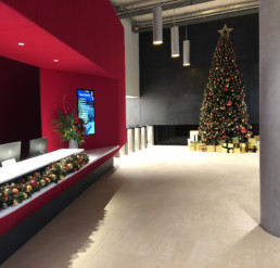 Photograph of a 16ft artificial Christmas tree decorated in Nordic theme decorations with a gold star: orange, red, grey and gold baubles with artificial red berries, cinnamon sticks, pinecones and oranges. Beneath the tree are gold presents wrapped in ribbon. On the left-hand side is a red reception desk with a garland decorated in the same baubles. Office Christmas Decor; Christmas decorations, Christmas florist, Office decorations, Xmas decorations, Christmas tree, Artificial Christmas tree, Real Christmas tree. Office Christmas; Christmas decorators Wreath making; bespoke Christmas Decor.