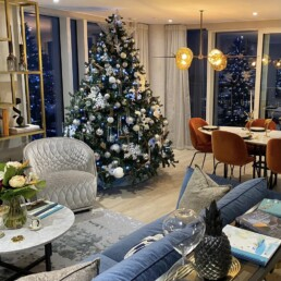 Photograph of an 8ft artificial Christmas Tree decorated in Frozen Woodland decorations: silver and white baubles of assorted sizes, with silver twigs, snowflakes, white iridescent hanging strings of pearls, white feathers, cinnamon sticks and pinecones. The Christmas tree is situated in a show home, beside a dining table with velvet orange chairs, a living area with silver rug and blue sofa, and a gold shelving unit. Office Christmas Decor; Christmas decorations, Christmas florist, Office decorations, Xmas decorations, Christmas tree, Artificial Christmas tree, Real Christmas tree. Office Christmas; Christmas decorators Wreath making; bespoke Christmas Decor