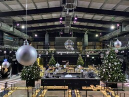 Photograph of an installation view at Boxpark Wembley, four real 14ft Christmas trees decorated in bespoke black and white decorations, with silver twigs and silver stars. Hanging from the ceiling are silver glitter, matt and shiny baubles on individual strings. Office Christmas Decor; Christmas decorations, Christmas florist, Office decorations, Xmas decorations, Christmas tree, Artificial Christmas tree, Real Christmas tree. Office Christmas; Christmas decorators Wreath making; bespoke Christmas Decor.