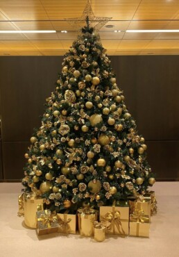 Photograph of an 8ft artificial Christmas tree decorated with all gold theme decorations and a gold star; gold and glitter baubles, gold roses, berries, pinecones and holly. Beneath the tree are gold presents tied with matching ribbons. Office Christmas Decor; Christmas decorations, Christmas florist, Office decorations, Xmas decorations, Christmas tree, Artificial Christmas tree, Real Christmas tree. Office Christmas; Christmas decorators Wreath making; bespoke Christmas Decor.