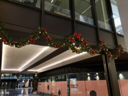 Photograph of a swagged garland and matching wreath hanging from the exterior of a building. The decorations are All Natural themed; with red bows, natural dried oranges, red berries, cinnamon sticks and apple pieces. Office Christmas Decor; Christmas decorations, Christmas florist, Office decorations, Xmas decorations, Christmas tree, Artificial Christmas tree, Real Christmas tree. Office Christmas; Christmas decorators Wreath making; bespoke Christmas Decor