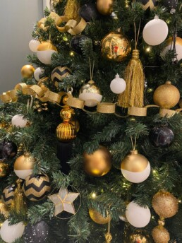 Photograph of a close-up of an artificial Christmas tree decorated in Art Deco theme decorations with gold, brown and black baubles with gold berries and gold eucalyptus. Office Christmas Decor; Christmas decorations, Christmas florist, Office decorations, Xmas decorations, Christmas tree, Artificial Christmas tree, Real Christmas tree. Office Christmas; Christmas decorators Wreath making; bespoke Christmas Decor