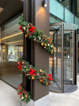 Photograph of a garland wrapped around the external pillar of a building, next to a revolving door. The decorations are All Natural themed; with red bows, natural dried oranges, red berries, cinnamon sticks and apple pieces. Office Christmas Decor; Christmas decorations, Christmas florist, Office decorations, Xmas decorations, Christmas tree, Artificial Christmas tree, Real Christmas tree. Office Christmas; Christmas decorators Wreath making; bespoke Christmas Decor